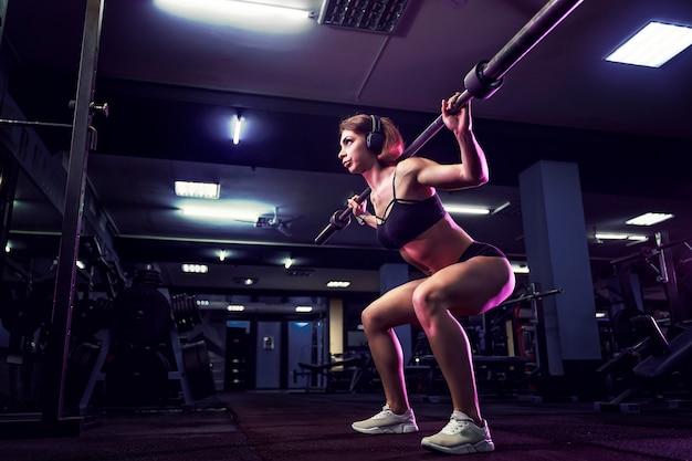 Atrakcyjne dopasowanie seksowna kobieta na siłowni kuca ze sztangą. kobieta trenuje z powrotem
