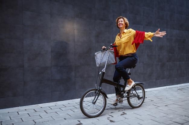 Atrakcyjne dopasowanie zdrowa modna blondynka kaukaski starszy kobieta jedzie na rowerze i macha.