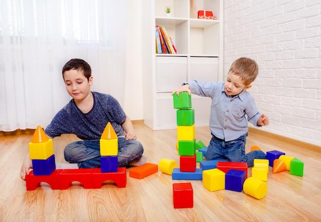 Atrakcyjne dzieci bawiące się z konstruktorem na podłodze w domu. dzieci w wieku przedszkolnym zabawy. żłobek, rozwój dzieci. na podłodze kolorowe plastikowe klocki.