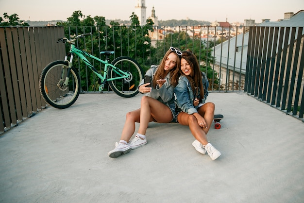 Atrakcyjne dziewczyny nawiązujące połączenie wideo na smartfonie i czujące się szczęśliwe w nowoczesnym parku miejskim.