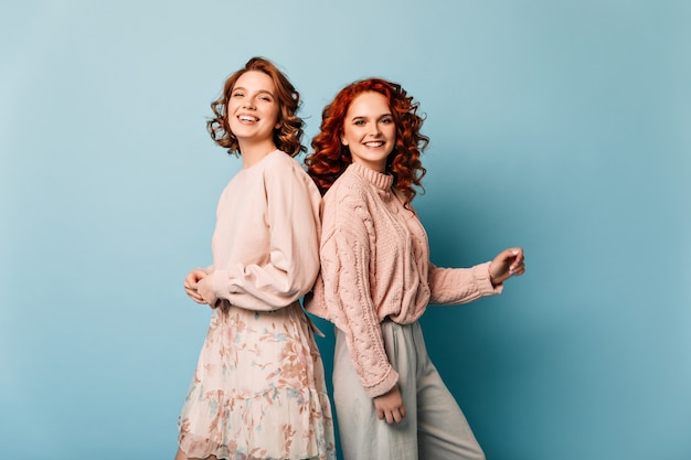 Atrakcyjne dziewczyny pozują z uśmiechem na niebieskim tle. strzał studio koleżanek wyrażających pozytywne emocje.