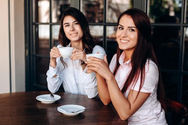 Atrakcyjne dziewczyny pozuje w kawiarni, pijąc słodką kawę. przepływ pracy