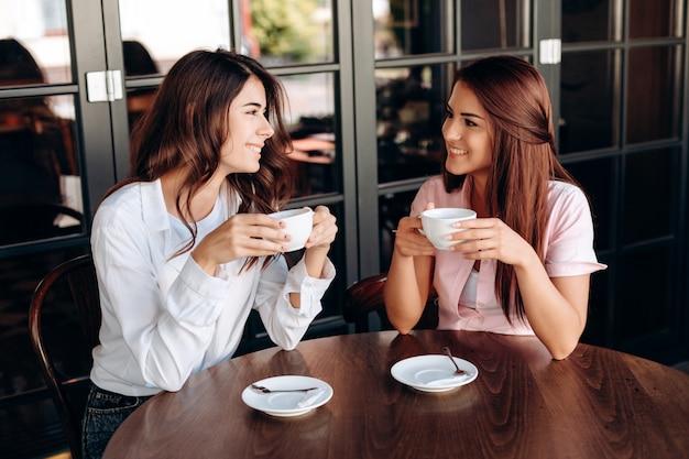 Atrakcyjne dziewczyny rozmawiają ze sobą w kawiarni na lunch biznesowy