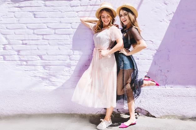 Atrakcyjne dziewczyny w długie letnie sukienki pozowanie na jednej nodze i uśmiechnięte