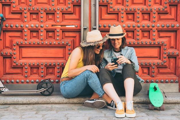 Atrakcyjne i fajne kobiety para lesbijek patrząc telefon komórkowy i uśmiechając się nawzajem na czerwonym tle drzwi. szczęście tej samej płci i radosna koncepcja.