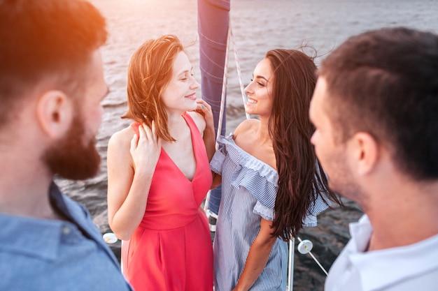 Atrakcyjne i niesamowite młode kobiety stoją razem i patrzą na siebie. uśmiechają się. mężczyźni stoją przed nimi i patrzą na kobiety.
