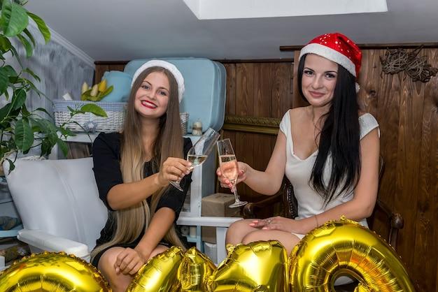 Atrakcyjne i piękne dziewczyny w kapeluszach z kieliszkami szampana