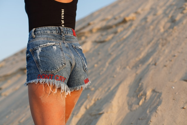 Atrakcyjne kobiece pośladki w skrócie na piaszczystej plaży. seksowna młoda dziewczyna w jeansowych szortach plenerowych.