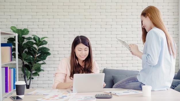 Atrakcyjne mądrze kreatywnie azjatyckie biznesowe kobiety w mądrze przypadkowej odzieży pracuje na laptopie podczas gdy siedzący