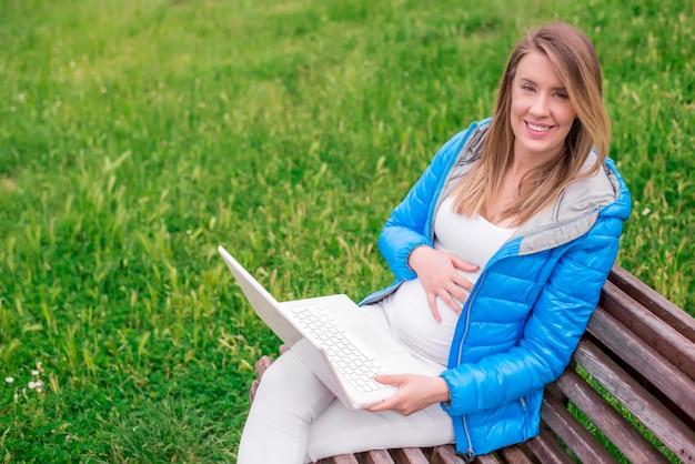 Atrakcyjne młoda kobieta z toothy smile przy użyciu komputera przenośnego na zewnątrz pomieszczeń
