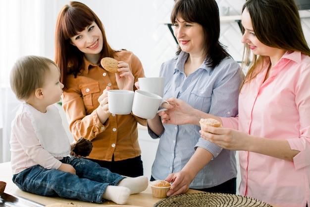 Atrakcyjne młode kobiety, kobieta w średnim wieku i mała śliczna córka gotują w kuchni. kochająca rodzina je babeczki w kuchni i pije kawę