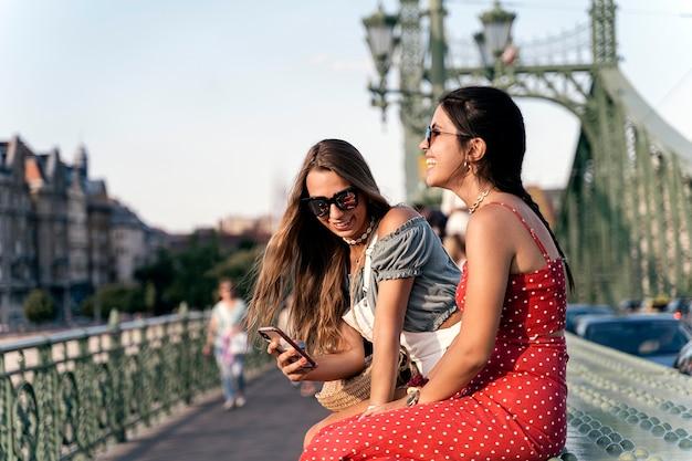 Atrakcyjne młode koleżanki w letnich ubraniach i okularach przeciwsłonecznych, siedzące na ławce na moście i śmiejące się