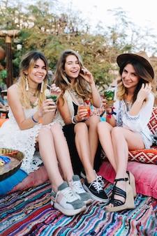 Atrakcyjne młode uśmiechnięte dziewczyny w modnych sukienkach spędzają razem czas na letnim pikniku w parku