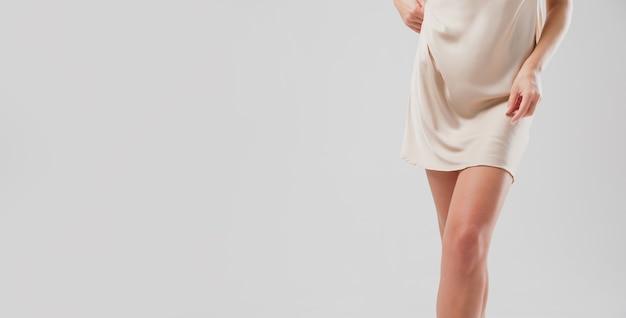 Atrakcyjne nogi kobiety w jedwabnej koszulce nocnej. pełen wdzięku kobieca postać w bieliźnie z miejsca na kopię
