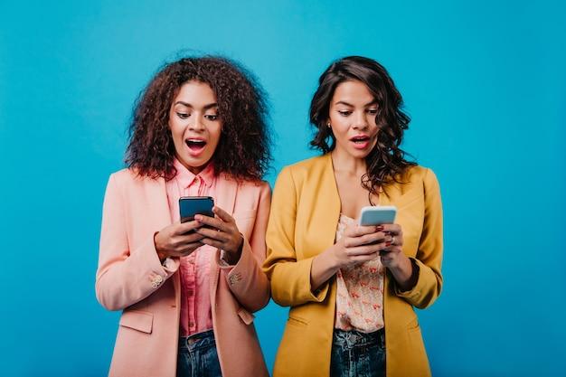 Atrakcyjne panie w jasnych ubraniach korzystające z telefonów