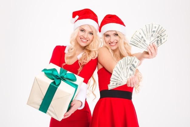 Atrakcyjne radosne blond siostry bliźniaczki w czerwonych sukienkach i czapkach świętego mikołaja pozują z pieniędzmi i prezentem na białym tle