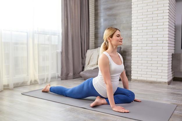 Atrakcyjne, sportowe momtobe rozciągające nogi podczas treningu w domu