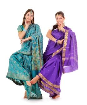 Atrakcyjne stojące dwie kobiety w tradycyjne niebieskie i fioletowe indyjskie ubrania. tancerze dotykają stopy pokazując element tańca. na białym tle