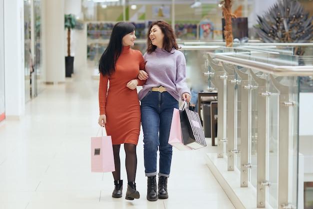 Atrakcyjne szczęśliwe młode kobiety w centrum handlowym, spacery i uśmiechnięte, trzymając torby na zakupy