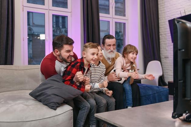 Atrakcyjne trzy pokolenia ludzi, jak ojciec, dziadek i wnuki, którzy siedzą na wygodnej kanapie w domu i spędzają wolny czas oglądając mecz piłki nożnej, krzycząc, gdy drużyna zdobywa piłkę.