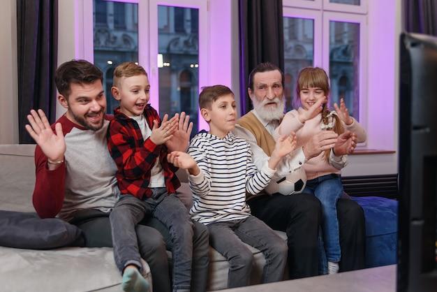 Atrakcyjne trzy pokolenia ludzi jako ojciec, dziadek i wnuki siedzące na wygodnej kanapie w domu