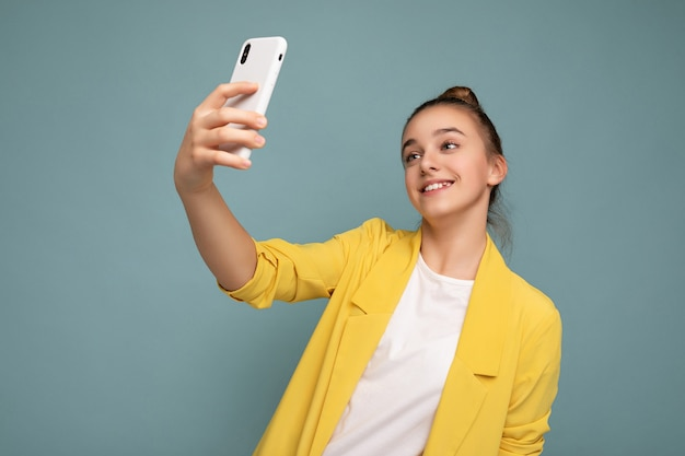 Atrakcyjne urocze młode uśmiechnięte szczęśliwe dziewczyny trzymając telefon komórkowy i przy użyciu telefonu komórkowego, biorąc selfie na sobie stylowe ubrania na białym tle na tle ściany.