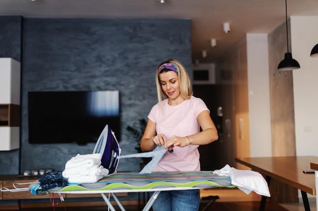 Atrakcyjne uśmiechnięte blond gospodyni stojącej w salonie i ubrania do prasowania.