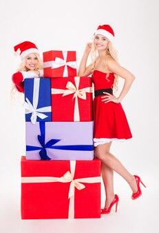 Atrakcyjne, wesołe młode kobiety w sukienkach i czapkach świętego mikołaja pozują z kolorowymi prezentami na białym tle