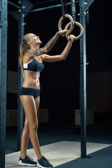 Atrakcyjne wysportowane sportsmenki odpoczywające na kółkach gimnastycznych na siłowni