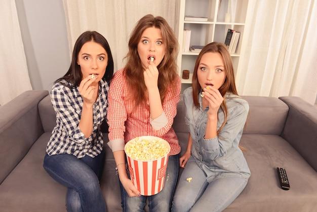 Atrakcyjne wystraszone dziewczyny oglądają film i jedzą popcorn