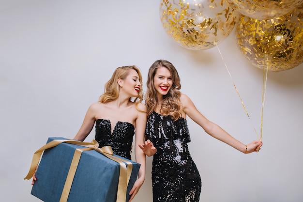 Atrakcyjne ypung kobiety w czarnych luksusowych sukienkach świętują urodziny z wielkim prezentem i balonami. podekscytowana, bawiąca się, czarująca modelka, świętująca, uśmiechnięta.
