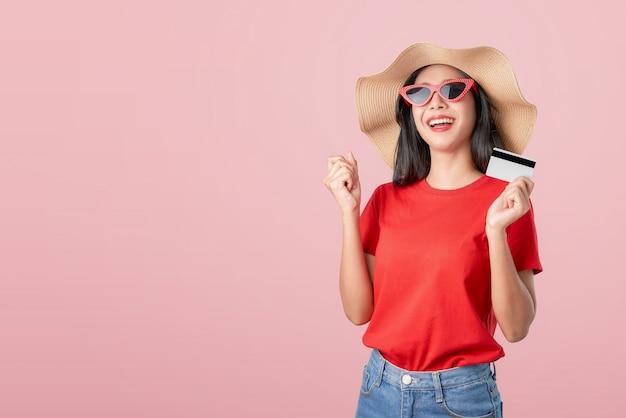 Atrakcyjnego uśmiechu azjatycka kobieta trzyma płatność kartą kredytową i zadziwiał dla sukcesu na pomarańcze.