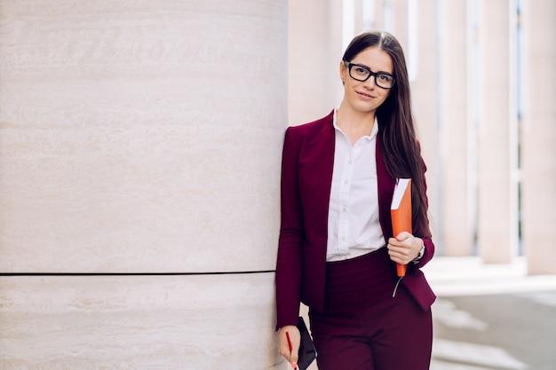 Atrakcyjnej brunetki biznesowa kobieta w bordowym kostiumu i szkłach trzyma dzienniczek i smartphone jest w dobrym nastroju. koncepcja ludzie biznesu. zdjęcie z pustym miejscem na reklamę.