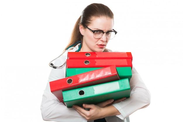 Atrakcyjnej caucasian brunetki kobiety lekarki smutna pozycja w biurze z segregatorami w jej rękach na bielu