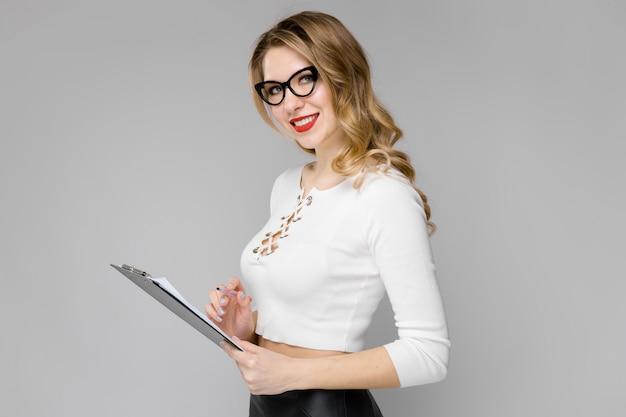 Atrakcyjnej młodej blondynki biznesowa kobieta w czarny i biały ubraniach trzyma mienie schowka uśmiechniętą pozycję w biurze na szarość