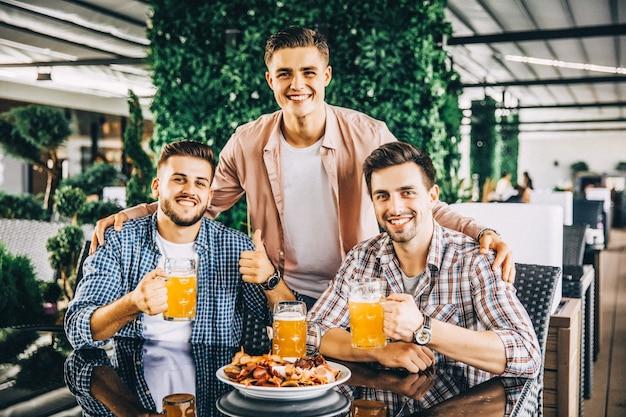 Atrakcyjni chłopcy pijący piwo w kawiarni na letnim tarasie