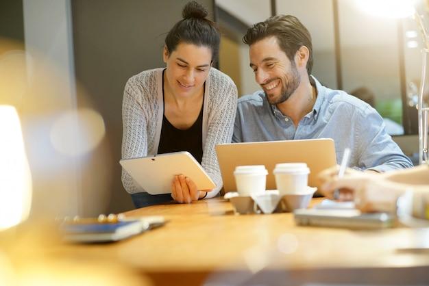 Atrakcyjni koledzy dzielący się pomysłami biznesowymi w przestrzeni roboczej