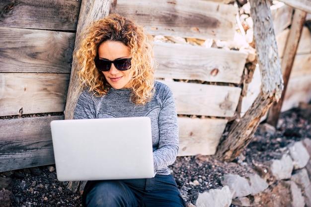 Atrakcyjni ludzie dorosła blondynka używa laptopa. komputer na zewnątrz - podłączony wszędzie i cyfrowy styl życia nomadów - koncepcja pracowników w plenerze bez biura