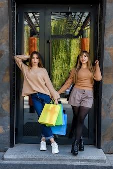 Atrakcyjni szczęśliwi klienci z paczkami po zakupach pozują na zewnątrz
