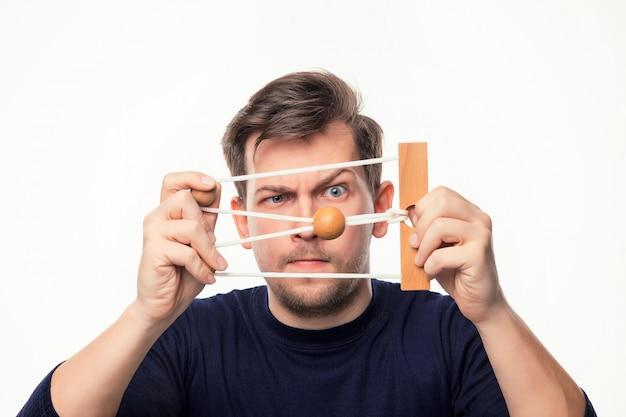 Atrakcyjny 25-letni biznesmen patrząc zmieszany na drewniane puzzle.