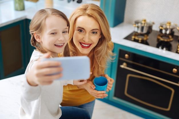 Atrakcyjny alert blond młoda matka uśmiecha się i trzyma filiżankę herbaty, podczas gdy jej córka robi zdjęcia