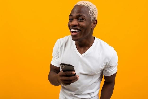Atrakcyjny amerykanin w białej koszulce trzyma telefon na żółtym tle