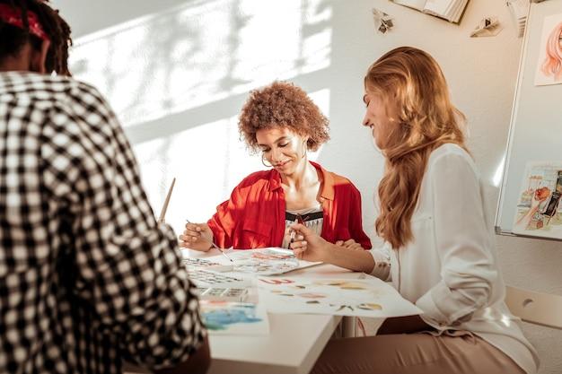 Atrakcyjny artysta. szczupła, atrakcyjna artystka, ubrana w beżowe spodnie i białą bluzkę, siedząca obok przyjaciół