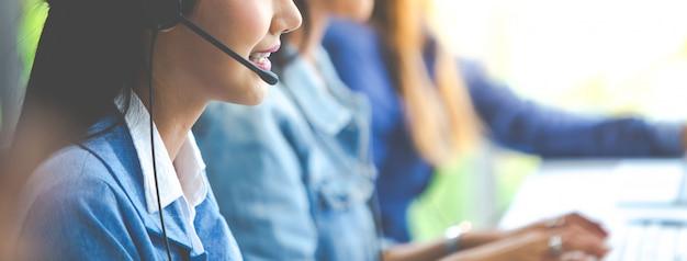 Atrakcyjny azjatycki biznes kobieta w garniturach i zestawach słuchawkowych uśmiecha się podczas pracy z komputerem w biurze. asystent obsługi klienta pracuje w biurze