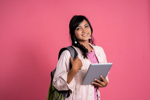 Atrakcyjny azjatykci żeńskiego ucznia mienia pastylki komputer osobisty