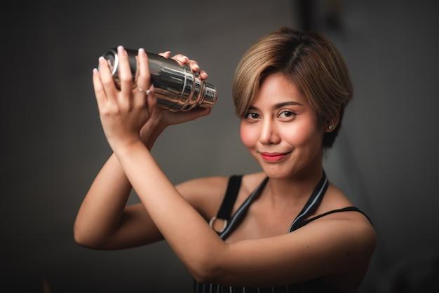 Atrakcyjny barman dziewczyna trzyma w dłoniach stalowe shakery do koktajli w barze
