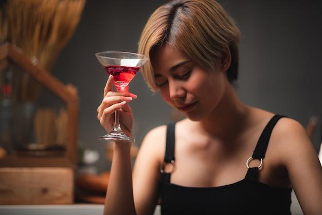 Atrakcyjny barman dziewczyna trzyma w dłoniach świeży koktajl w barze na kontuar do świętowania