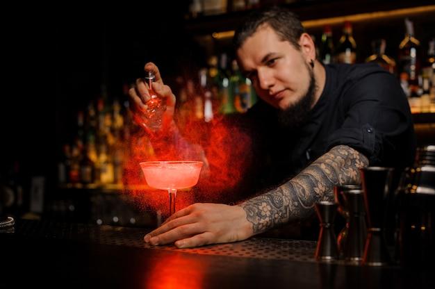 Atrakcyjny barman spryskujący pyszny koktajl ze specjalnego waporyzatora na blacie barowym