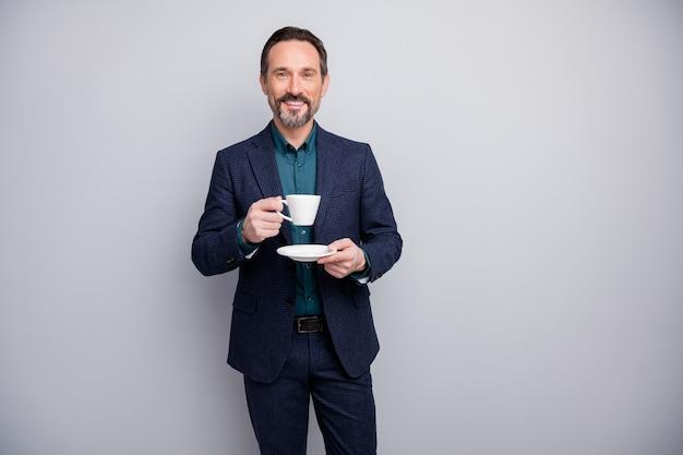 Atrakcyjny biznes dojrzały mężczyzna dobrze ubrany kierownik pije kawę