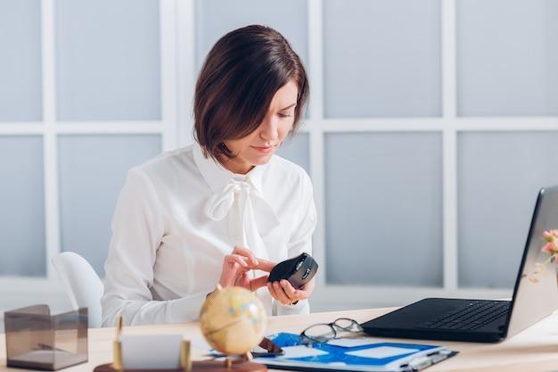 Atrakcyjny biznes kobieta pracuje i zmienia baterie w myszy w biurze.